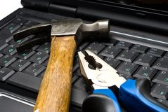 Hammer and pliers on a laptop Stock Image