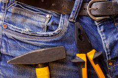 Hammer and pliers lie on blue working jeans trousers stock images