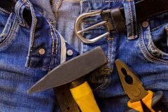 Hammer and pliers lie on blue working jeans trousers Stock Image