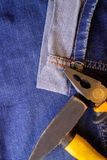 Hammer and pliers lie on blue working jeans trousers royalty free stock images