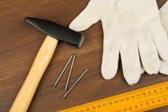 Hammer, protective gloves and three nails Royalty Free Stock Photo