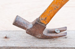 hammer pulling out a nail out of a piec Stock Photo