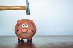 Hammer above a Piggy bank royalty free stock images