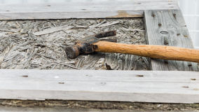Hammer rests on wood box. Old hammer with wood handle rests on wood box Stock Photo