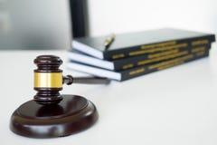 Hammer Richterhammer mit legalem Buch auf braunem hölzernem Schreibtisch mit Spindel Lizenzfreies Stockfoto