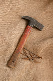 Hammer, rusty nails on the background of rough cloth. Stock Photos