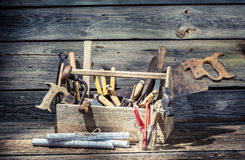 Hammer, saw and paper scheme in the carpentry toolbox Royalty Free Stock Image