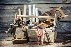 Hammer, saw and paper scheme in the carpentry workbench Stock Photos