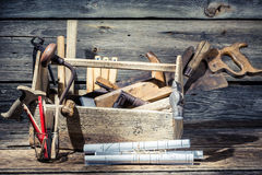 Hammer, saw and paper scheme in the carpentry workshop Royalty Free Stock Images