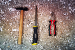 Hammer, saw and pliers on rubble. Pile Royalty Free Stock Images