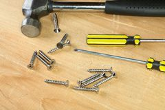 Hammer screw-driver screws on a  board Stock Photos