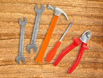 Hammer, screwdriver and wrenches over wooden Stock Images