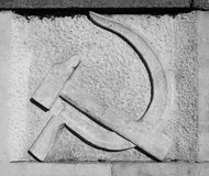 Hammer and sickle. Communist hammer and sickle symbol on stone. Black and white picture stock photos