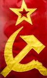 Hammer and Sickle on Old Russian Flag. Hammer and sickle and star on an old flag from the U.S.S.R stock photo