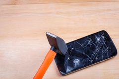 Hammer on a smartphone with a broken screen. On a wooden background. Close-up. A heavy construction hammer lies on a modern black smartphone with a broken royalty free stock image