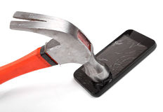 Hammer and smartphone with smashed display Royalty Free Stock Photography