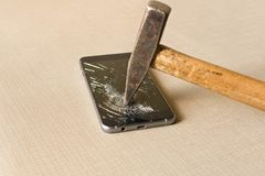 A hammer smashing a mobile phone on a grey background stock photos
