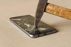 A hammer smashing a mobile phone on a grey background royalty free stock image