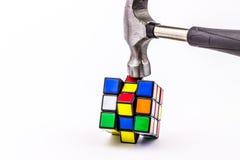 Hammer smashing Rubik cube. On a white background Royalty Free Stock Photo
