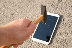 Hammer smashing the screen of a smartphone Stock Image