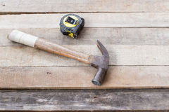 Hammer , tape measure. Hammer, tape measure and saw on wood Royalty Free Stock Photo