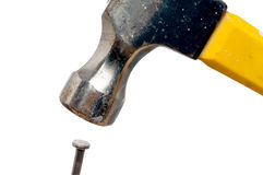 A hammer about to hit the nail on the head Royalty Free Stock Images