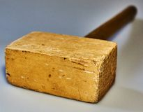 Wooden hammer on  background. A hammer from a tree lies on an  background. The hammer was used in the work. There are traces of blows. An object, a beater, an Royalty Free Stock Photo