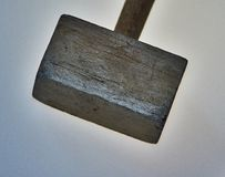 Wooden hammer on  background. A hammer from a tree lies on an  background. The hammer was used in the work. There are traces of blows. An object, a beater, an Stock Image