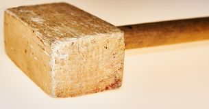 Wooden hammer on an  background. A hammer from a tree lies on an  background. The hammer was used in the work. There are traces of blows. An object, a beater, an Stock Images