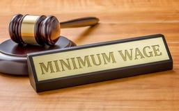 Hammer und ein Namensschild mit dem Stich Mindestlohn Lizenzfreies Stockfoto