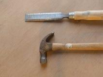 Hammer und Meißel auf Holztischhintergrund Stockbilder