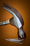 Hammer und Nägel auf einem hölzernen Hintergrund Lizenzfreie Stockbilder