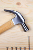 Hammer und Nägel auf hölzernem Hintergrund Lizenzfreies Stockbild