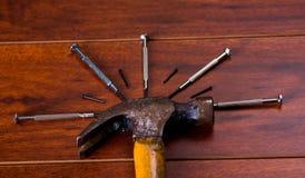 Hammer und Nägel auf Holztischhintergrund Lizenzfreies Stockbild