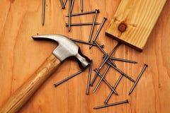 Hammer und Nägel auf Sperrholz Lizenzfreie Stockbilder