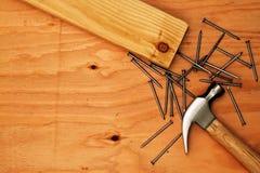 Hammer und Nägel auf Sperrholz Stockfotografie