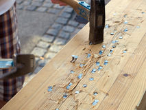 Hammer und Nägel im Holz Stockfotografie