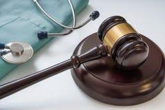Hammer und Stethoskop im Hintergrund Medizinrechte und Rechtsauffassung Lizenzfreie Stockfotos