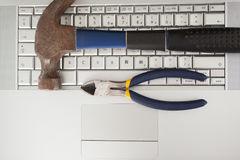 Hammer und Zangen auf Tastatur Stockfotografie
