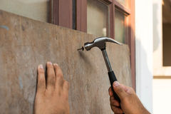 Hammer will arrive on nail by man. For strip window with wood plate Royalty Free Stock Image