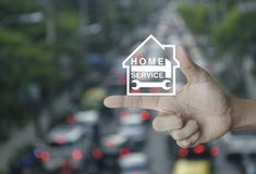 Home service concept. Hammer and wrench with house icon on finger over blur of rush hour with cars and road, Home service concept Stock Photography