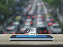 Home service concept. Hammer and wrench with house icon on modern smart phone screen on wooden table over blur of rush hour with cars and road, Home service Royalty Free Stock Photography