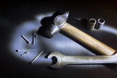 Hammer, wrench and nails on black background, light brush Stock Photo