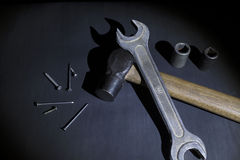 Hammer, wrench and nails on black background, light brush Stock Photos