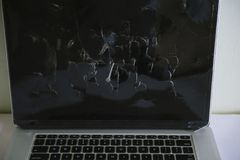 Hammered nails into a laptop close up. Clogged nail in a laptop close-up. Nail in the monitor screen stock image
