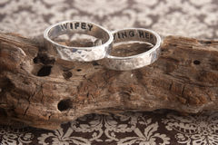 Hammered Rings on Driftwood and Paper. Two hammered sterling silver engagement rings on a piece of driftwood with a decorative paper for background Royalty Free Stock Photos