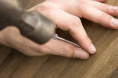 Hammering. Hand hammering a nail into a piece of wood Royalty Free Stock Images