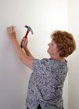 Hammering. A woman hammers a nail into a wall Royalty Free Stock Images