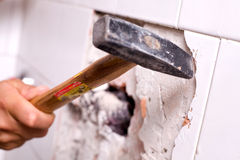 Hammering away on wall tiles. Hands using a hammer to remove white tiles from the wall in a DIY home improvement project stock images