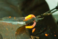 Hammering glowing steel - to strike while the iron is hot. Royalty Free Stock Photo